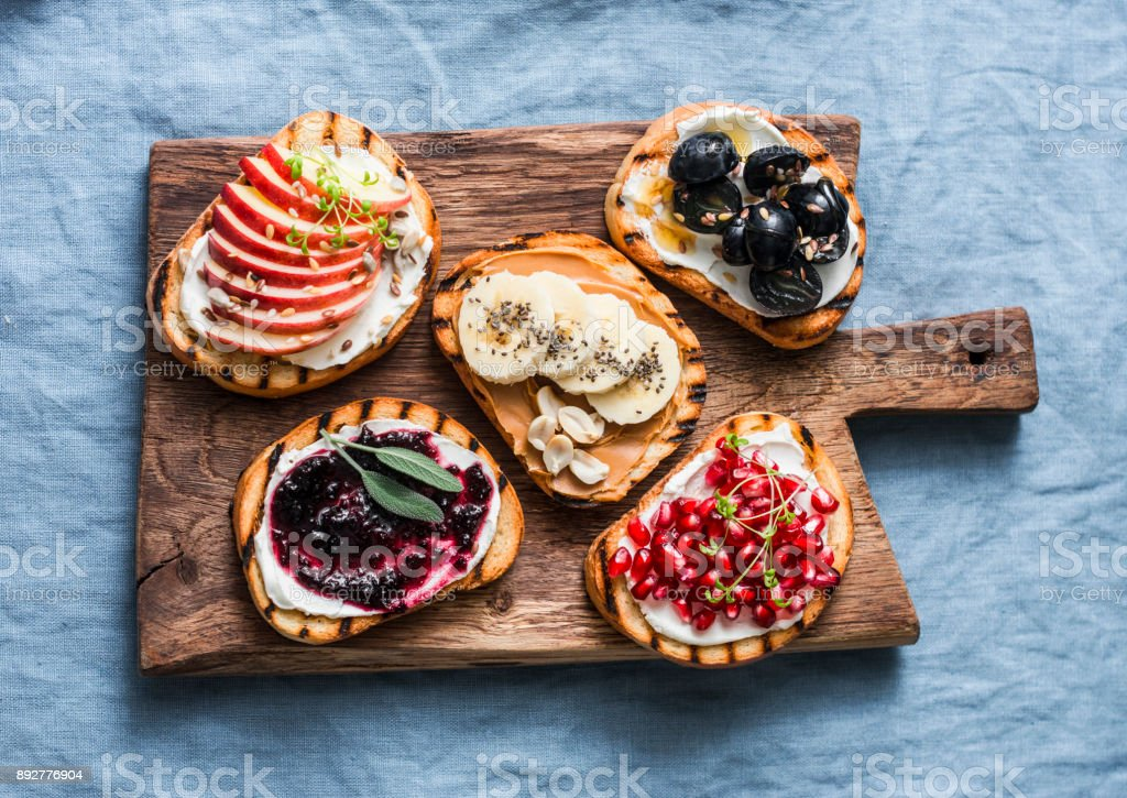 Variety grilled bread dessert small plates sandwiches with cream cheese and apple, pomegranate, jam, grapes, peanut butter, banana, flax seed, chia, nuts on a rustic cutting board on blue background, top view. Flat lay. Delicious breakfast or snack stock photo