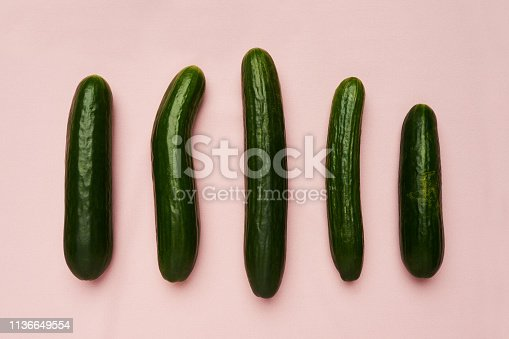 Studio shot of a row of cucumbers against a pink background