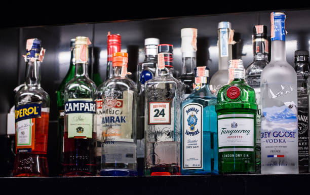 A variety of alcoholic beverages, Bernd, are placed on shelves in the bar for cocktails. - foto stock