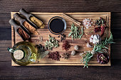 Variety of allspice ingredients and condiments for food seasoning on table in old fashioned kitchen. Ingredients set on a large size cutting board