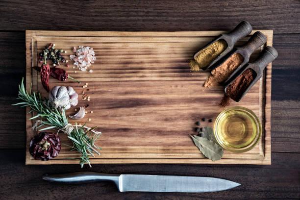 Variété d'ingrédients et de condiments d'épices pour assaisonnement alimentaire sur planche à découper dans une cuisine à l'ancienne - Photo
