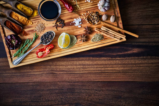 Variety of allspice ingredients and condiments for food seasoning on cutting board in old fashioned kitchen stock photo