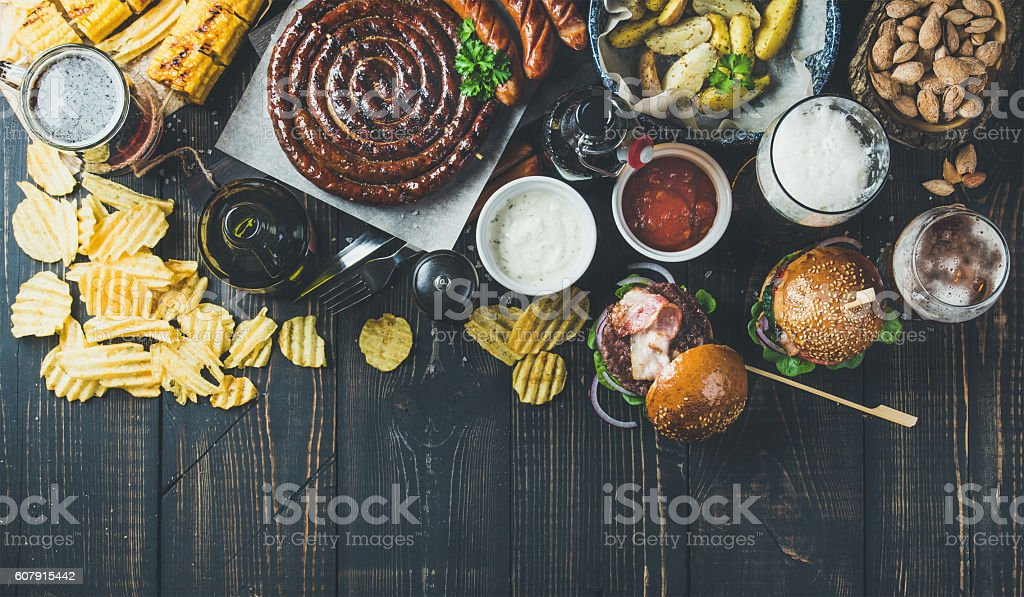 Variety of beers, sausages, burgers, potato, corn on dark background stock photo