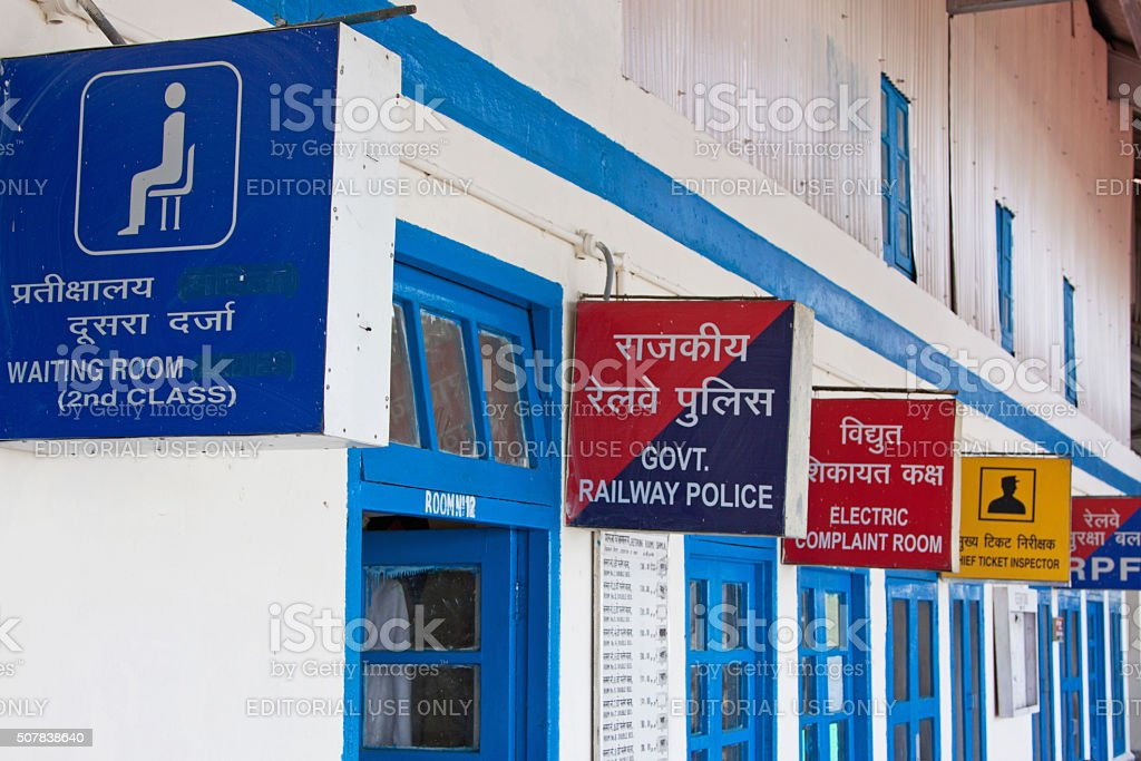 Variety of bilingual signs on an Indian railway station platform stock photo