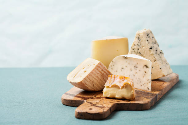 variety of cheeses on serving board - formaggio foto e immagini stock