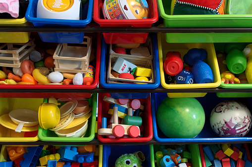 Many children's toys separated and organized in colorful bins.