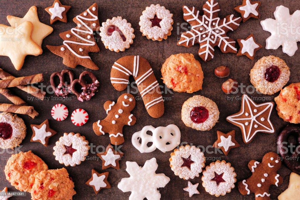 Variety of Christmas cookies and baked sweets, top view over a dark stone background Variety of Christmas cookies and sweets. Top view over a dark stone background. Holiday baking concept. Above Stock Photo