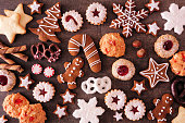 Variety of Christmas cookies and sweets. Top view over a dark stone background. Holiday baking concept.