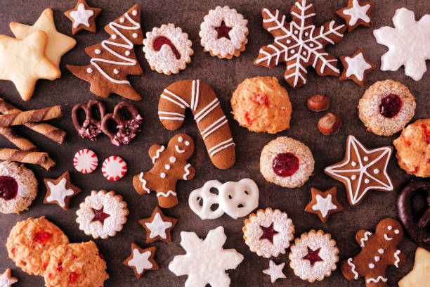 Variety of Christmas cookies and baked sweets, top view over a dark stone background stock photo