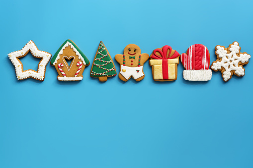 A variety of Christmas gingerbread in a row on a blue background. Top view, flat lay, copy space. The concept of the holiday