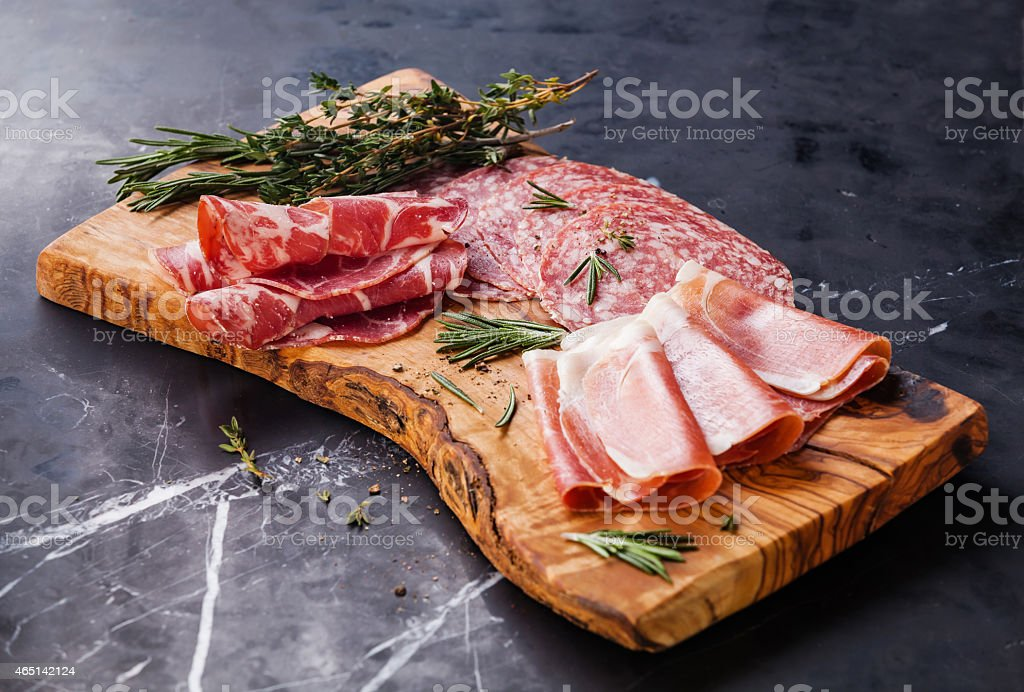 Variety of cold meats on a wooden board stock photo