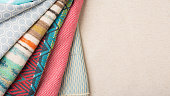 A variety of colorful fabrics folded and laid out over a canvas table with copy space for text.