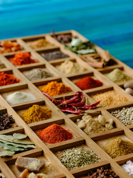 Variety of colorful, organic, dried, vibrant Indian food spices in a wooden tray on an old turquoise colored wood background, with atmospheric lighting. Many colorful, organic, dried, vibrant Indian food, ingredient spices including; chili powder, turmeric, cinnamon, star anise, coriander seeds, ground coriander, cumin seeds, ground cumin, cloves, asafoetida, fennel seeds, ground fennel, garam masala, fenugreek seeds, fenugreek leaves, curry leaves, green cardamom, white cardamom, black cardamom, nutmeg, bay leaf, mace, saffron and black mustard seeds displayed in white ceramic dishes on an old turquoise colored wood background, with atmospheric lighting. garam masala stock pictures, royalty-free photos & images