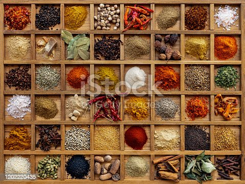 Many colorful, organic, dried, vibrant Indian food, ingredient spices displayed in a wooden compartment tray. Shot directly above, nice color contrast.