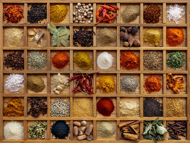 Variety of colorful, organic, dried, vibrant Indian food spices in a wooden compartment box. stock photo