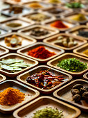Many colorful, organic, dried, vibrant Indian food, ingredient spices displayed in wooden trays on an old wooden background. Shot from a high angle, nice color contrast. Shallow depth of field.