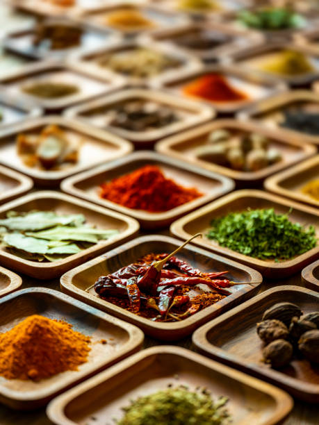 Variety of colorful, organic, dried, vibrant Indian food spices in wooden trays on an old wood background. Many colorful, organic, dried, vibrant Indian food, ingredient spices displayed in wooden trays on an old wooden background. Shot from a high angle, nice color contrast. Shallow depth of field. garam masala stock pictures, royalty-free photos & images