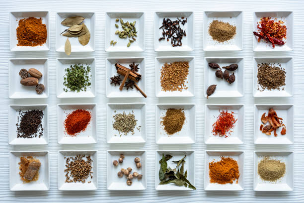 Variety of colorful, organic, dried, vibrant Indian food spices in white ceramic dishes on a white wood grain style table background. stock photo