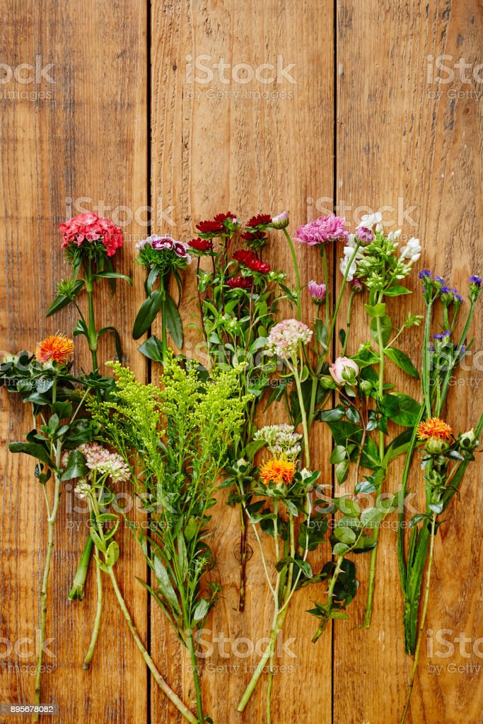 variety of colorful wild flowers on wooden table stock photo