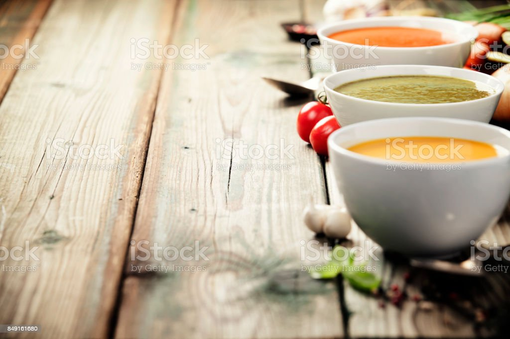 Variety of cream soups over old wood background stock photo