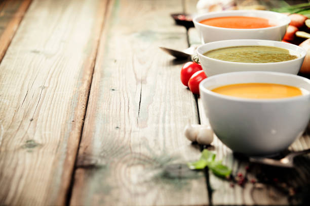 variety of cream soups over old wood background - zuppa foto e immagini stock