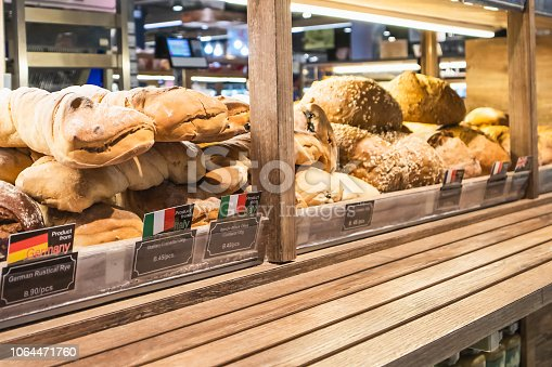 istock Variety of delicious breads displayed on shelves in bakery shop, Bangkok, Thailand 1064471760