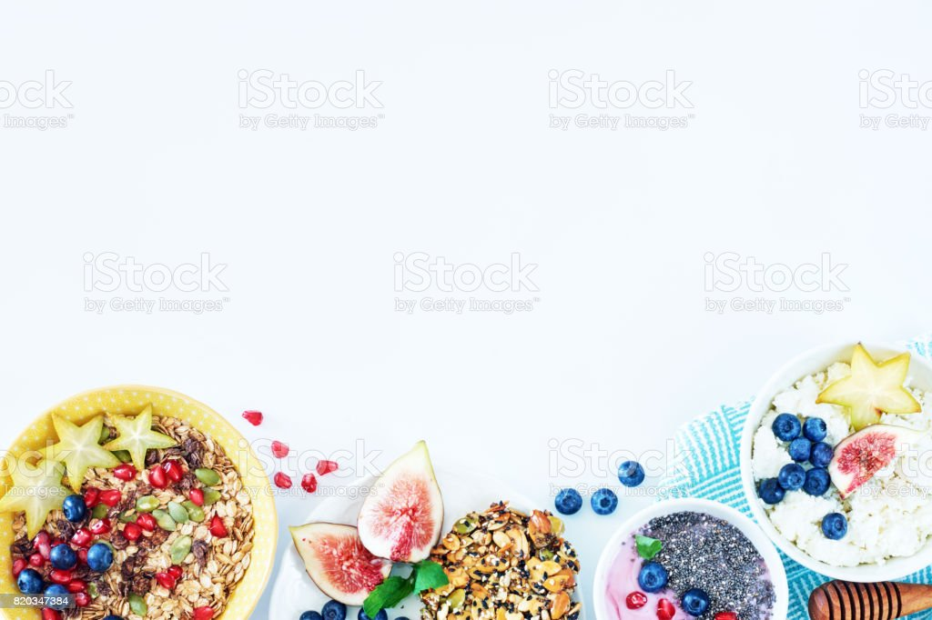 Variety of delicious breakfast dishes with fresh fruits and berries on a white table with a place for text. stock photo