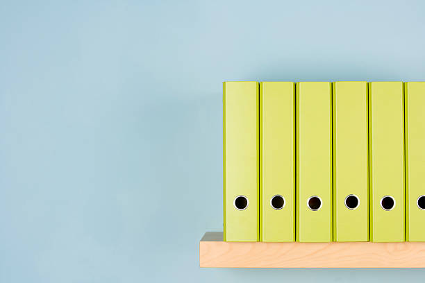 A variety of different green binders in a row on a shelf stock photo