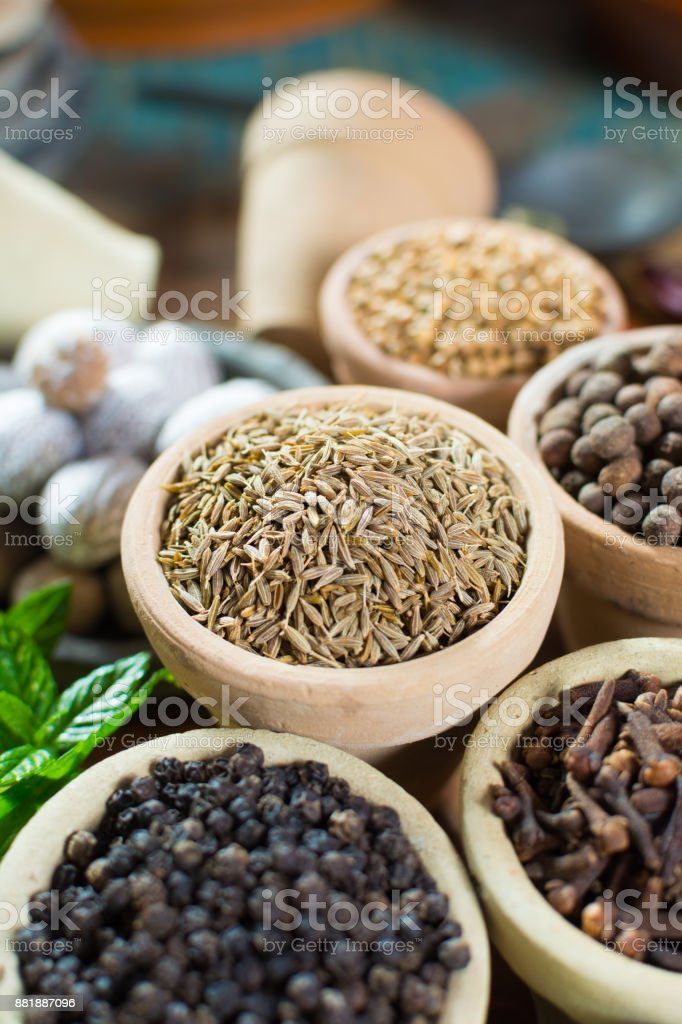 Variety of different spices with focus on ancient famous spice – dried whole cumin seeds with variety of another herbs and spices in Middle East style stock photo