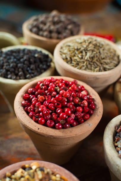 Variété d'épices différentes en mettant l'accent sur le poivre péruvien rose, faux poivre utilisé dans quatre poivres mélanges - Photo