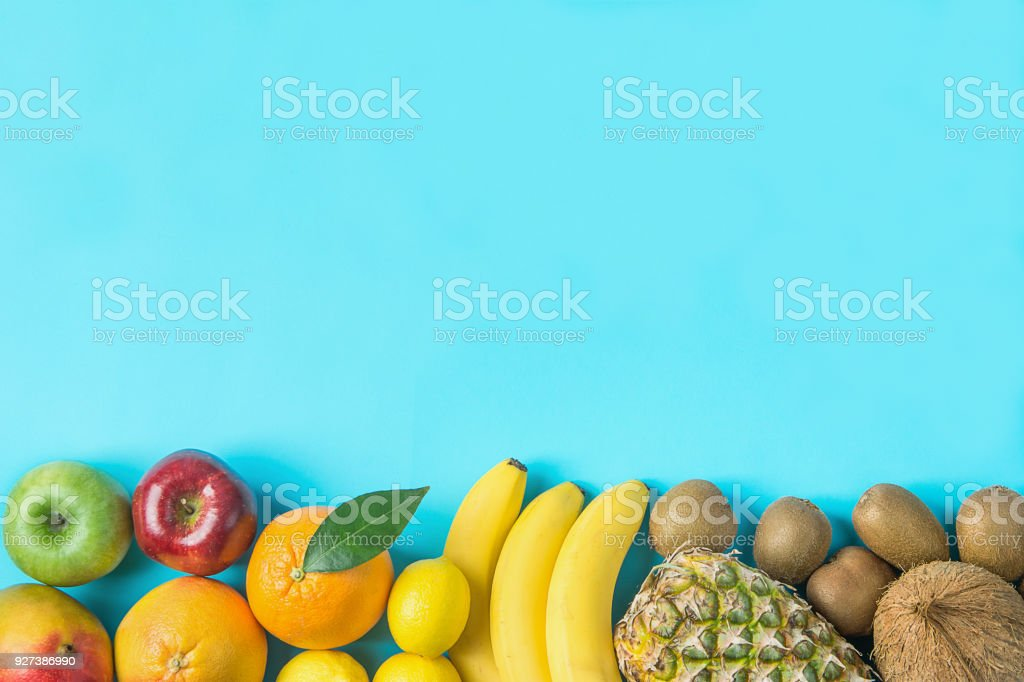 Variety of Different Tropical and Seasonal Summer Fruits. Pineapple Mango Coconut Citrus Oranges Lemons Apples Kiwi Bananas Arranged in Bottom Border on Blue Background.Healthy Lifestyle. Flat Lay stock photo
