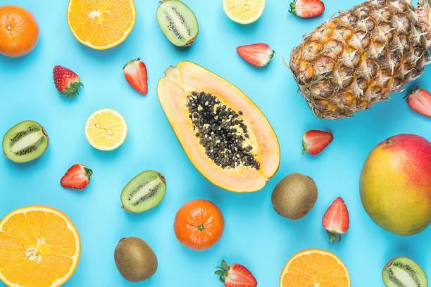 다른 열 대 계절 여름 과일의 다양 한입니다. 파파야 망고 귤 감귤 오렌지 파인애플 레몬 딸기 키 위 파란 배경에. 건강 한 라이프 스타일 다이어트 비타민입니다. 평면 배치 - 열대 과일 뉴스 사진 이미지