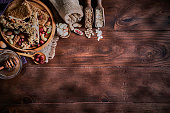Variety of dried fruit and nuts on a table in a old fashioned rustic kitchen making a frame with copy space