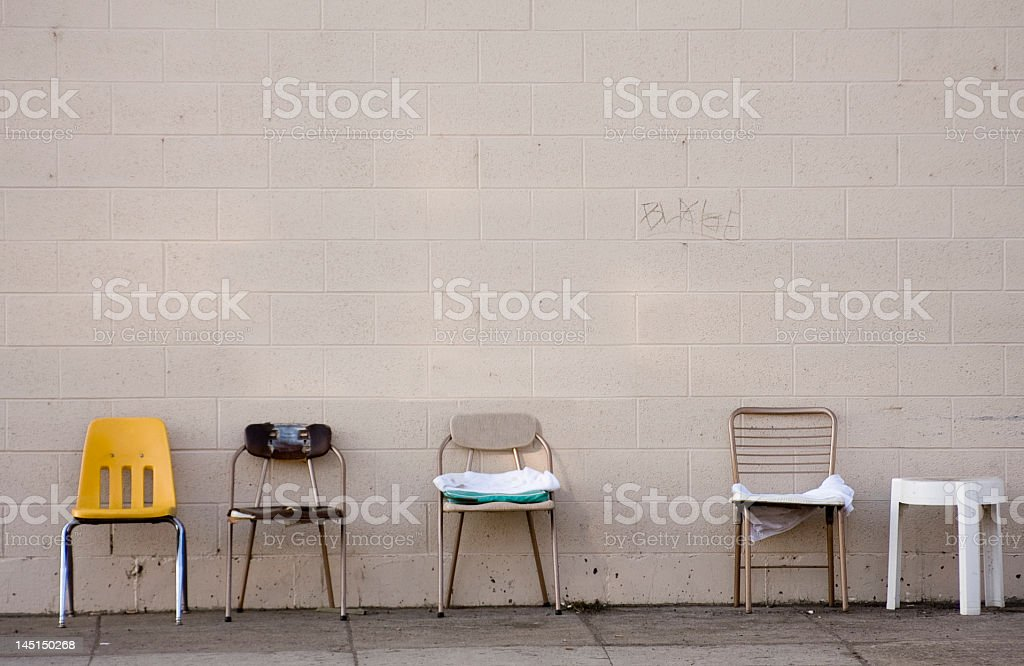 Variety of empty chairs along a painted wall stock photo