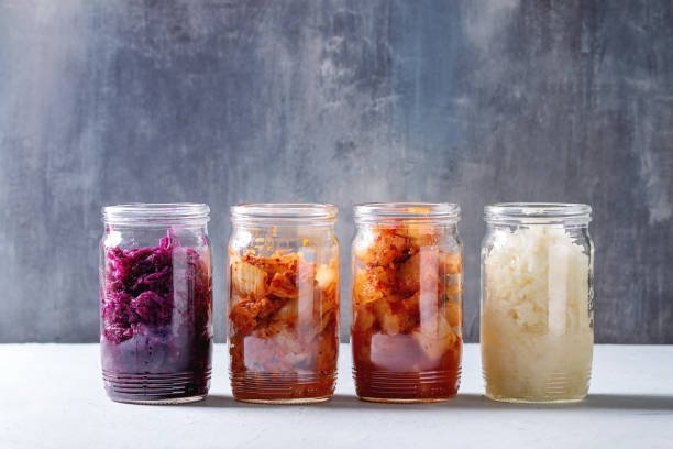 Variety of fermented food Variety of fermented food korean traditional kimchi cabbage and radish salad, white and red sauerkraut in glass jars in row over grey blue table. kimchee stock pictures, royalty-free photos & images