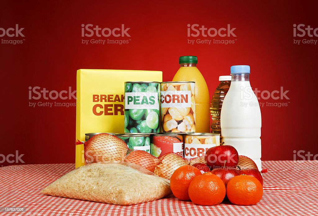 Variety of fresh and packaged basic foodstuffs against deep red royalty-free stock photo