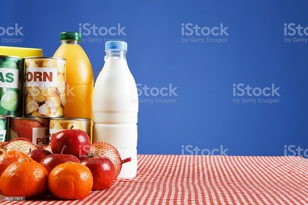 Variety of fresh and packaged food against blue background stock photo