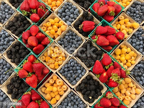 A variety of fresh berries are displayed in pint boxes in a market. The colorful display of fresh fruit in the spring.