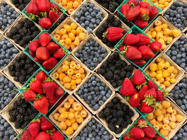 Variety of Fresh berries displayed in the market A variety of fresh berries are displayed in pint boxes in a market. The colorful display of fresh fruit in the spring. berry stock pictures, royalty-free photos & images