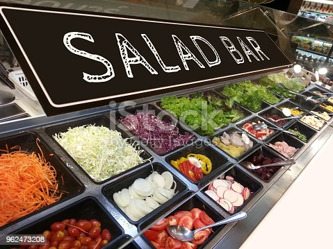 variety of fresh colorful vegetable and fruit at salad bar corner in supermarket with salad bar sign on top
