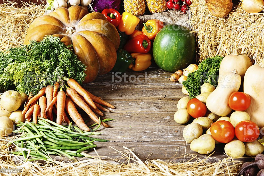 Variety of fresh fruit and vegetables arranged on weathered wood royalty-free stock photo