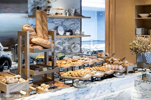 A variety of fresh homemade bread and bakery corner in luxury hotel breakfast buffet, restaurant interior.