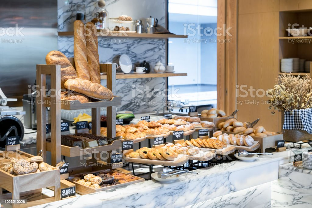 A variety of fresh homemade bread and bakery corner in luxury hotel breakfast buffet, restaurant interior. stock photo