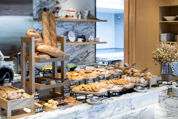 a variety of fresh homemade bread and bakery corner in luxury hotel breakfast buffet, restaurant interior. - panetteria foto e immagini stock