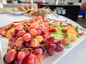 A variety of freshly prepared and arranged fruits presented on a plate in a real-world catering display.