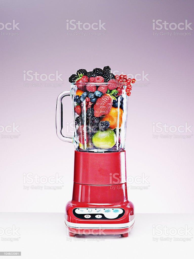 Variedad de frutas crammed en el mezclador - foto de stock