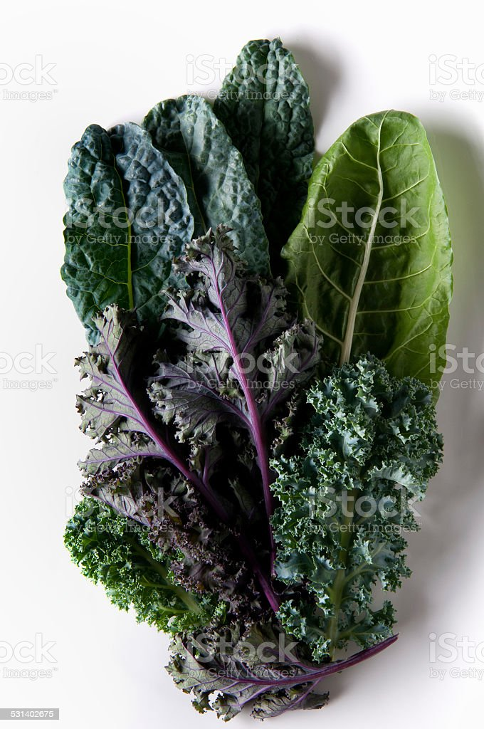 Variety of Green and Purple Kale Leaves on White Background stock photo