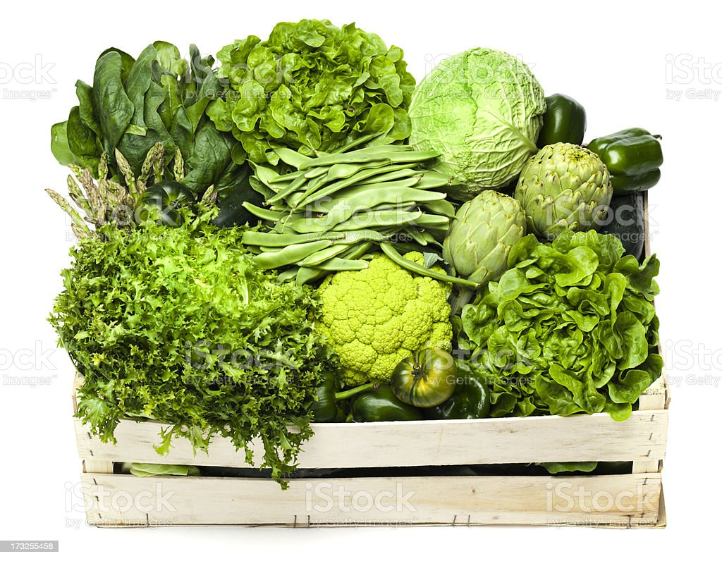 Variety of green vegetables sitting in a wooden box stock photo
