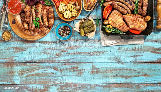685404620 istock photo Variety of grilled food on the blue wooden table on a sunny day 646085042