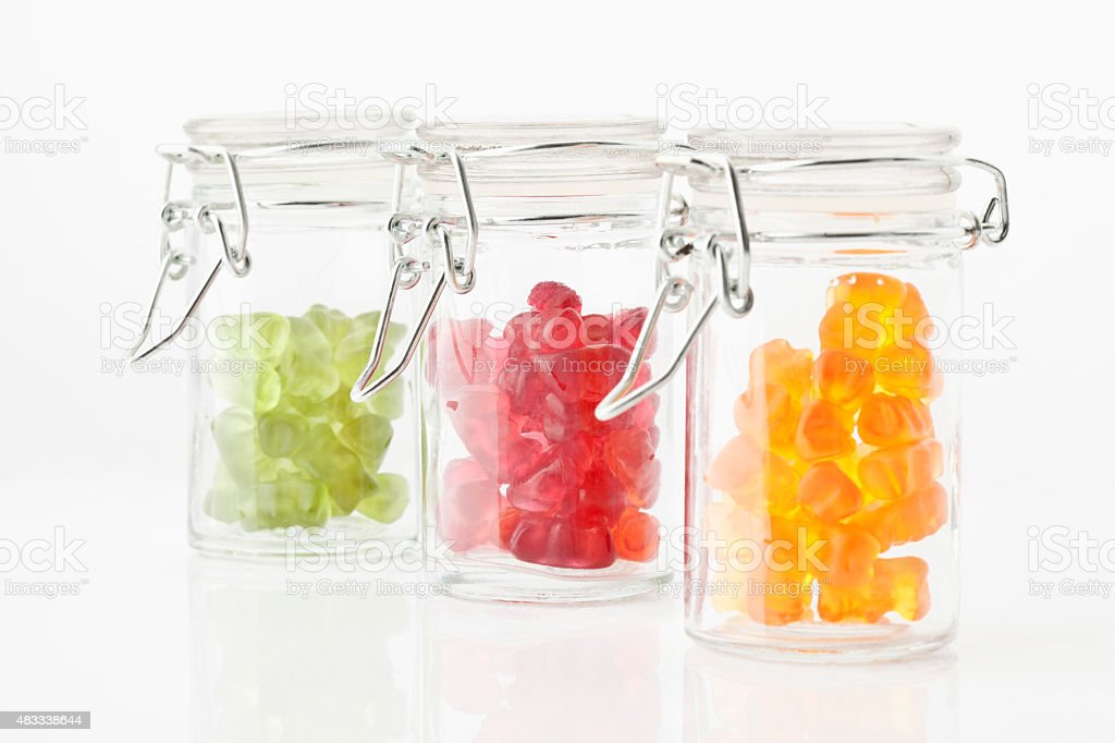 Variety of gummi bears in a preserving jar, white background stock photo